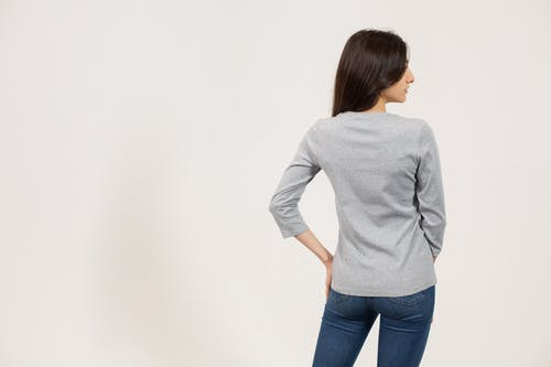 Back view of female model in jeans and gray long sleeve t shirt standing against white background and looking away