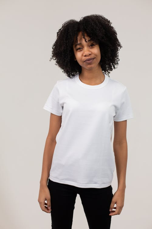 Charming African American female with curly hair wearing casual clothes standing against white background and looking at camera