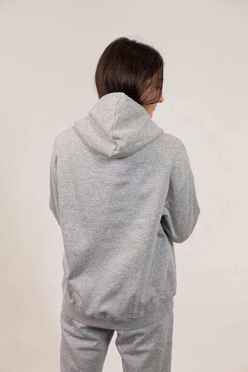 Back view of young female wearing oversize hoodie and sweatpants standing against white background