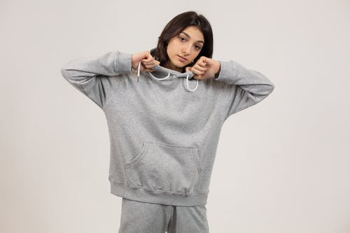 Serious female wearing oversize hoodie and sweatpants standing against white background and looking at camera