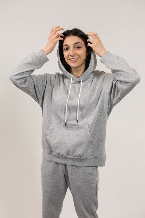 Smiling woman in sports suit putting hands on head