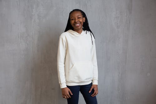 Smiling black woman in casual clothing standing near gray wall