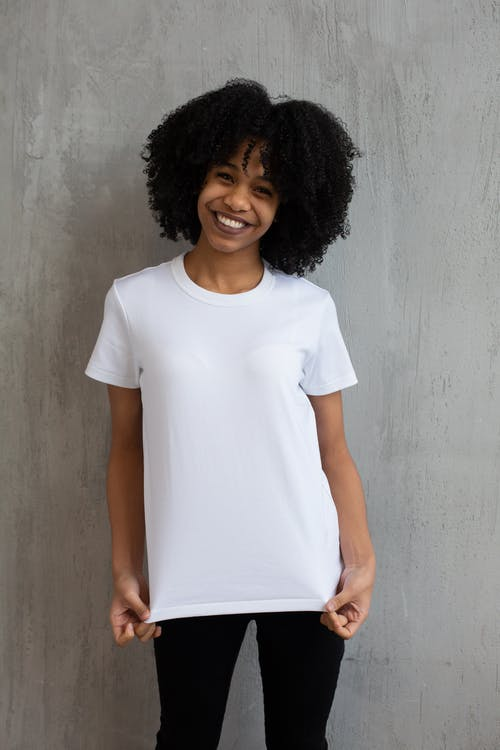 Charming African American female in white t shirt and tight pants smiling widely and looking at camera