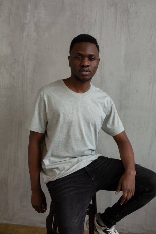 Serious black man in t shirt and jeans on chair