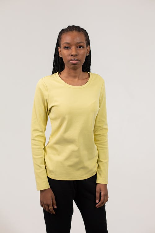 Unemotional African American female with long braids wearing long sleeve t shirt and pants against white background and looking at camera