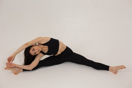 Flexible woman stretching body during training