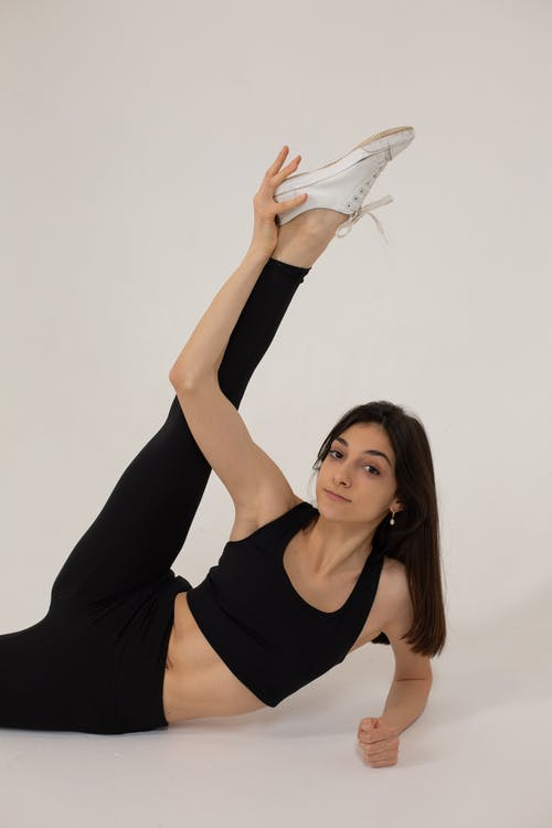 Flexible woman doing exercise for stretching in studio