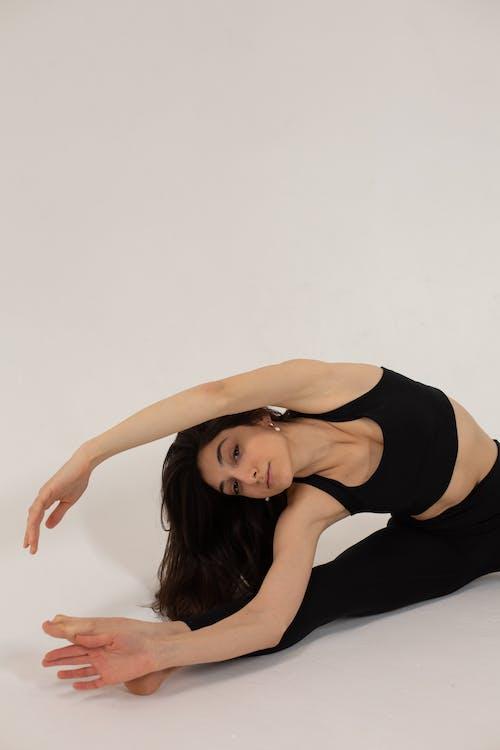 Graceful woman bending aside sitting in split