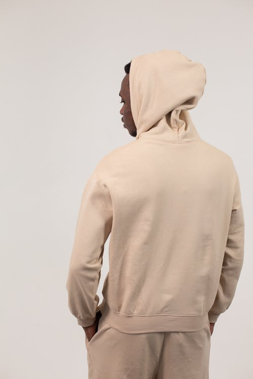 Back view of African American man in hoodie and sweatpants standing with hands in pockets against white background