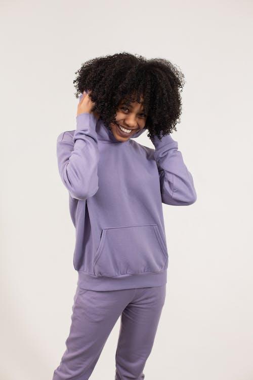 Smiling black woman in purple hoodie and sweatpants in studio