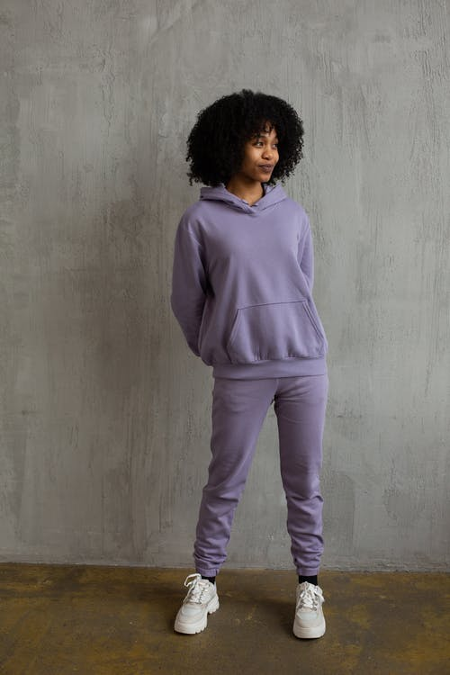 Full body of young African American female with curly hair in trendy violet sportswear holding hands behind back and looking away in modern studio