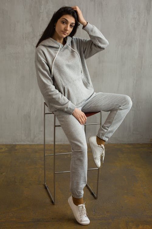 Stylish young woman in trendy sportswear in studio