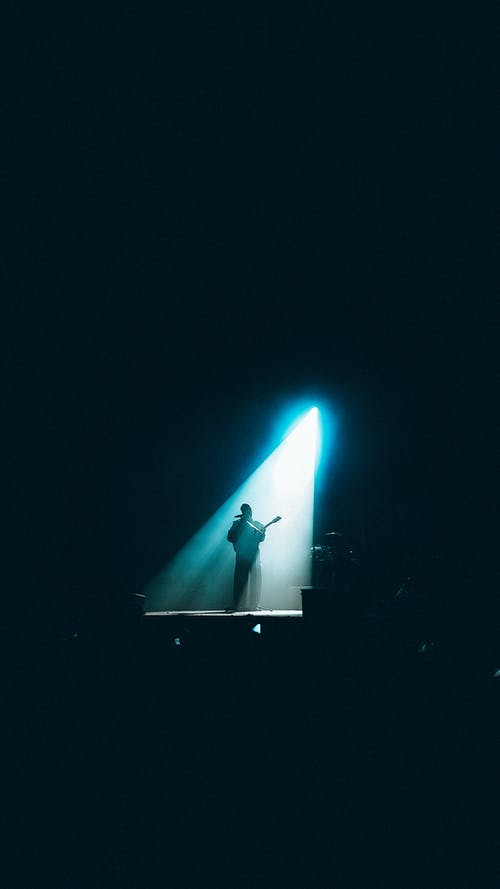 Man in Black Suit Standing on Stage
