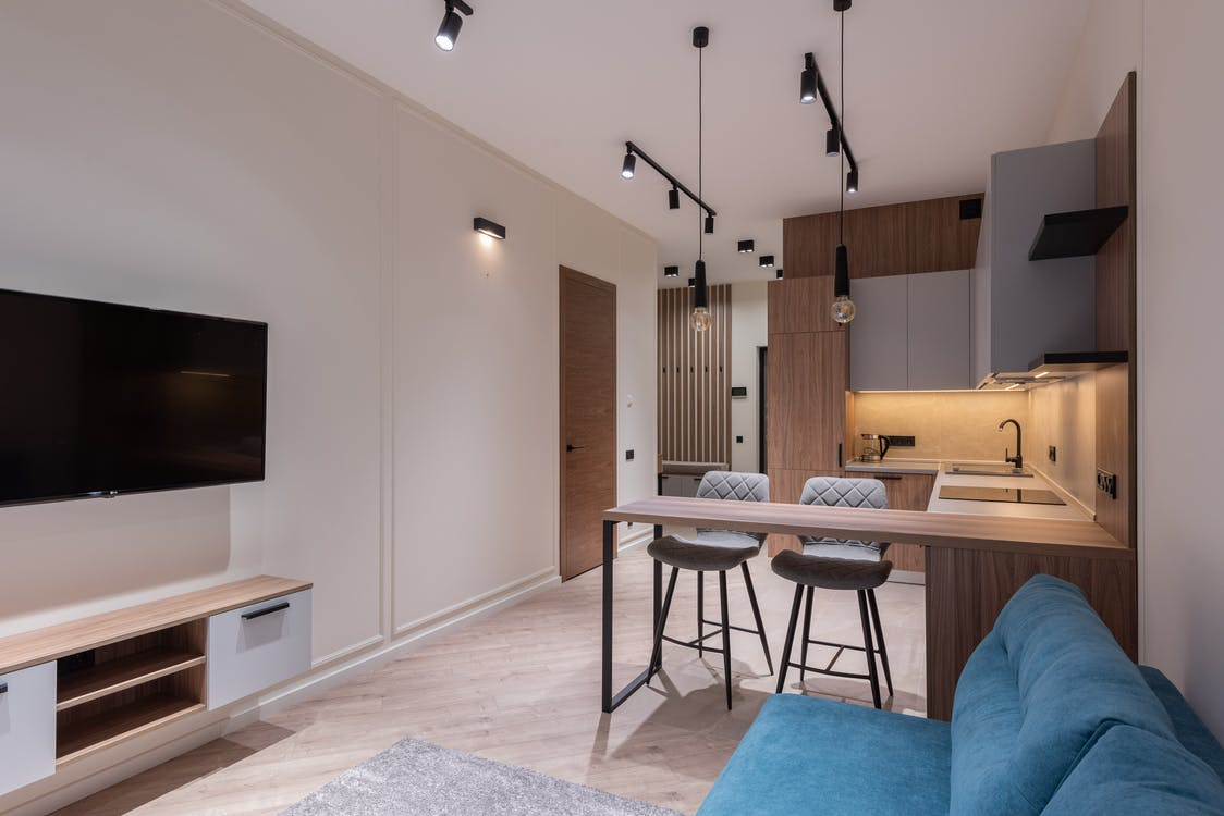 Interior of modern studio with kitchen furniture dining area and lounge with blue sofa