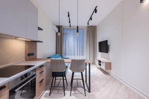 Interior design of modern spacious apartment with necessary furniture and appliances with TV set and air conditioner