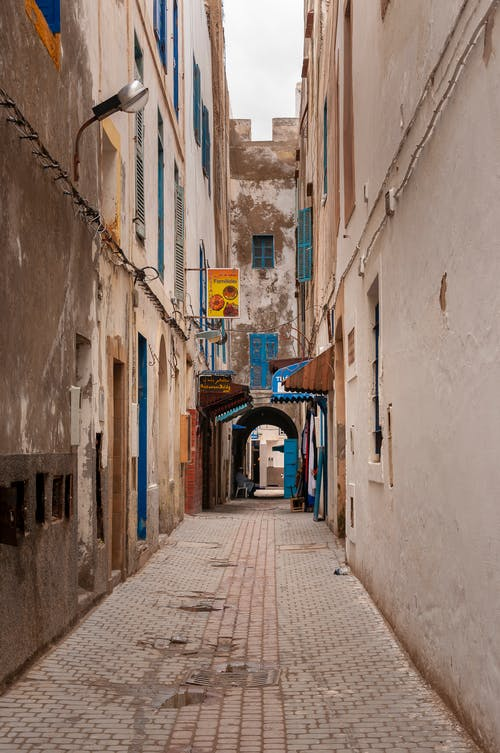 Old narrow street amidst weathered buildings in Morocco