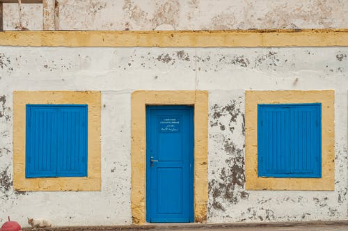 Old shabby building facade with blue door and windows