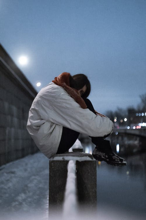 Side view of anonymous female teenager in warm clothes embracing knees on bridge above river in evening in winter
