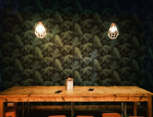 Can on Table Near Turned-on Lamp Sconces