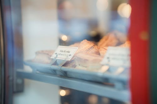 Through glass of assorted delicious desserts with prices placed on metal display of bakery shop on street on blurred background