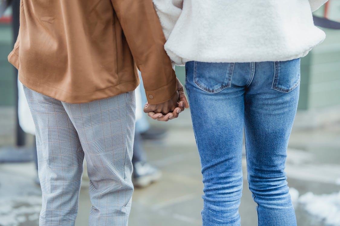 Мужчина и женщина, держась за руки во время прогулки по улице
