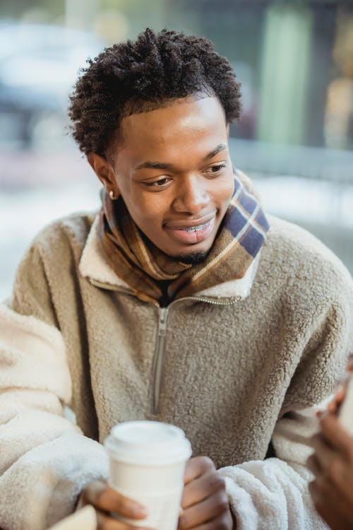 Positive African American male in warm clothes with paper cup of hot beverage sitting on terrace of cafe on blurred background