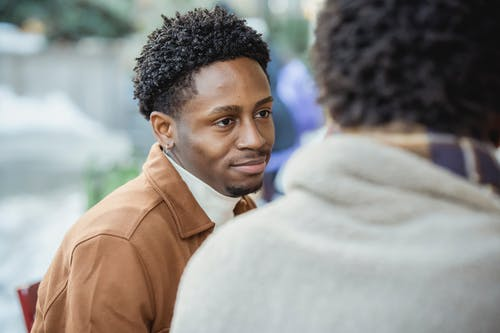 Cheerful African American male looking at faceless partner while sitting on terrace of cafe on street in city on blurred background