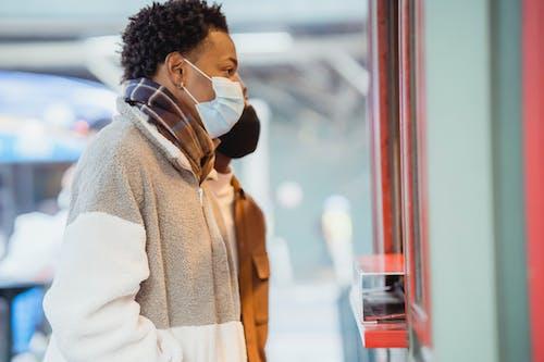 Black couple in medical masks choosing goods on street