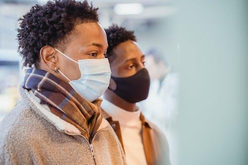 Attentive black men in medical masks standing on street