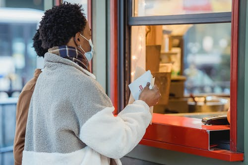 Side view of African American male couple in protective masks standing near window of store while ordering food on street on blurred background