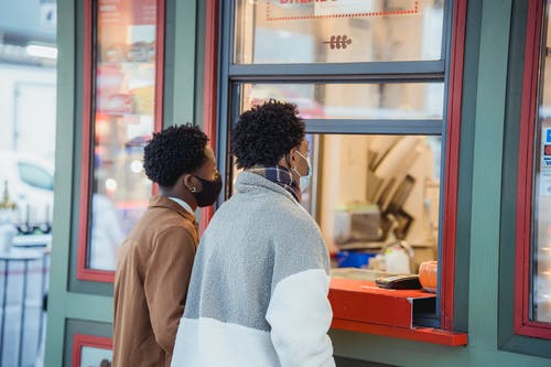 Side view of African American male in protective masks buying food while standing near window of store on street in city