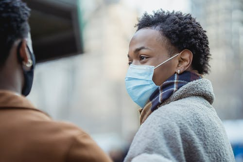 Black man in medical mask standing near anonymous man on street