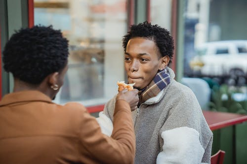 Anonymous man feeding cheerful African American boyfriend with tasty croissant while sitting on terrace of cafe in city on blurred background