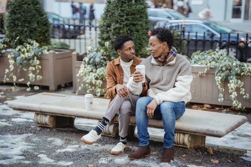 Full body of African American male couple with takeaway coffee looking at each other while sitting on bench on snowy street