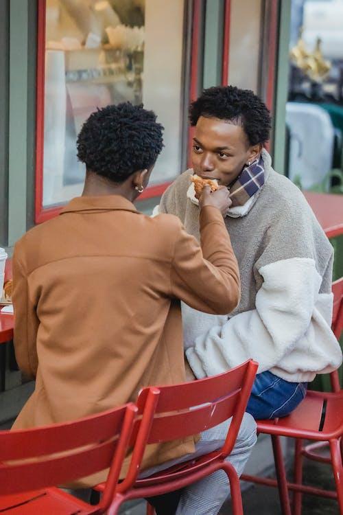 Faceless man feeding boyfriend with croissant