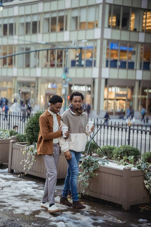 Full body of positive African American homosexual couple with takeaway coffee strolling on snowy pathway in city with building during date