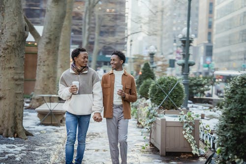 Cheerful African American homosexual couple with takeaway coffee holding hands and looking at each other while strolling on walkway on winter day