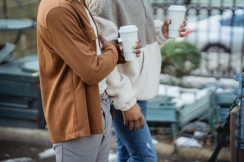 Crop black homosexual couple with coffee walking on street