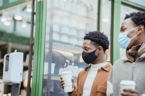 African American male couple with tasty takeaway hot beverages strolling on street near building while spending time together in city