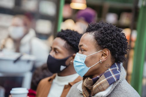Black men in medical masks on street