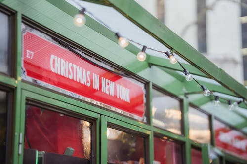 Low angle red signboard with Christmas In New York inscription hanging on glass showcase of shop on city street