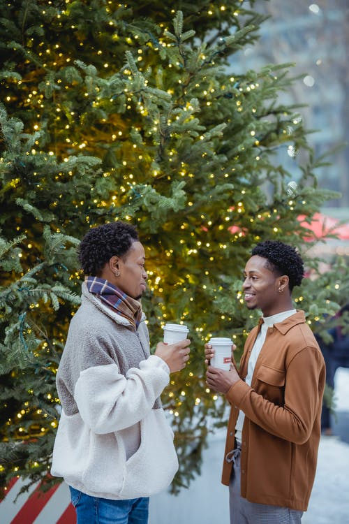 Side view of cheerful young stylish black male friends in trendy warm outfits smiling and chatting while drinking takeaway coffee standing on street near decorated Christmas tree