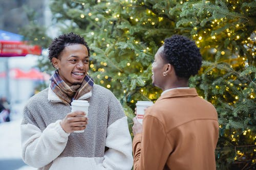Cheerful young black gays drinking coffee and laughing on street during Xmas holidays