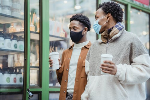 Stylish young African American male friends in warm clothes and medical masks walking on city street with coffee to go in hands and communicating