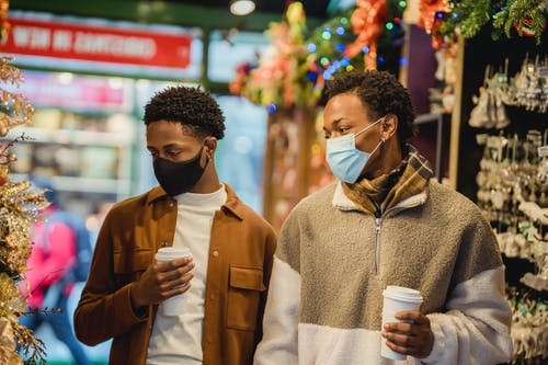 Stylish young African American guys walking in Christmas market with coffee to go
