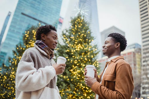 Low angle side view of positive young African American male friends in trendy clothes drinking takeaway coffee together on street and chatting during Xmas holidays in city