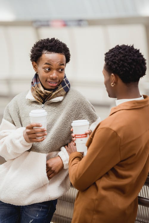 Black couple with cups of coffee having interesting communication