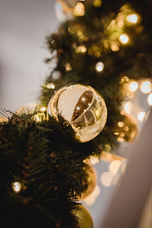 Christmas golden bauble on artificial fir garland full of lights on blurred background