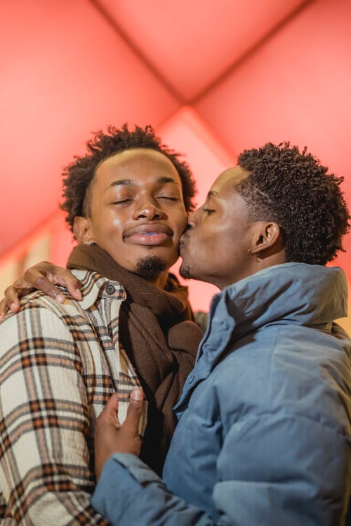 Tender African American homosexual man with closed eyes kissing cheerful black partner on cheek while standing on street during romantic date