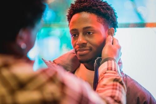 Crop anonymous African American male touching ears of smiling gentle boyfriend on glowing street